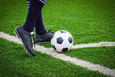 Foot kicking soccer ball on corner — Stock Photo