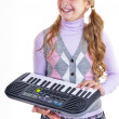 Schoolgirl playing on a small synthesizer — Stock Photo #12620551