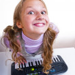 Schoolgirl playing on a small synthesizer — Stock Photo #12620569