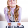 Schoolgirl playing on a small synthesizer — Stock Photo #12620574