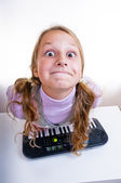 Schoolgirl playing on a small synthesizer — Stock Photo