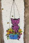 Painting Cat in the flower basket on the house wall — Zdjęcie stockowe