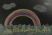 Color drawing rainbow over the city on the black background — Stock Photo