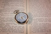 Pocket watch on the open book — Stock Photo