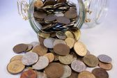 Coins spill out of the jar — Stock Photo