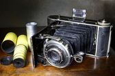 Antique bellows camera and original film — Stock Photo
