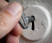 Hand with key in keyhole. — Stock Photo