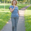Stock Photo: Beautiful woman walking in the park. Summer day.