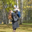 Mother holding a baby son in the autumn park — Stock Photo