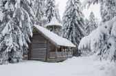 Wooden chapel in a snowy forest. Winter north. — Stockfoto