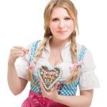 Bavarian woman in dirndl, holding lebkuchen. — Stock Photo #33236557