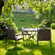 Beautiful garden with white table and chair — Stock Photo