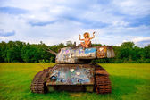Young woman posing on army tank. — Stock Photo