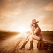 Stylish cowgirl on a sunset road — Stock Photo #47120377
