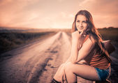 Smiling woman at sunset road — Stockfoto