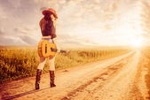 Cowgirl woth guitar on a road — Stock Photo