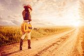 Cowgirl woth gitarre auf einer straße — Stockfoto
