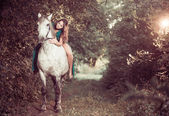 Woman ride white horse at forest path — Stock Photo