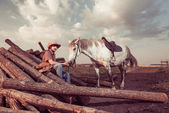 Cowboy and horse at summer sunset — Stock Photo