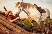 Cowboy and horse on a lumbers — Stock Photo