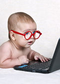 Funny kid in the glasses with a netbook — Stock Photo