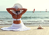 Woman in a hat sits on the beach. — Stock Photo
