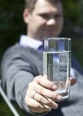El hombre sonriente sosteniendo un vaso de agua limpia — Foto de Stock