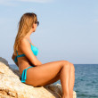Girl in swimsuit near the sea sitting on the big stone — Stock Photo #12819504