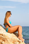 Girl in swimsuit near the sea sitting on the big stone — Stock Photo