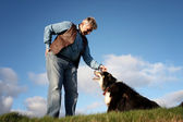 Mature man and a sheep dog — Stock Photo