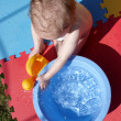A young child playing with water — Stock Photo
