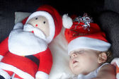 A young boy sleeping with santa — Stock Photo