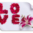 Love word made from red rose petals and lily flower on paper — Stock Photo #21648675