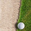 Golf ball on green grass near sand bunker — Stock Photo #9273716