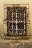 Old window with ornamental bars. — Stock Photo