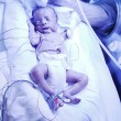 Infant irradiated with ultraviolet light - Stock Photo