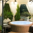 Covered hot tub in a garden - Stock Photo