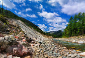 Rock slides near the river — Stock Photo