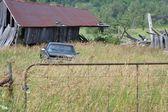 Oude schuur en vrachtwagen in veld — Stockfoto
