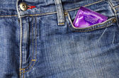 Condom and jeans — Stock Photo