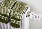 Knitted gloves on the radiator — Stockfoto
