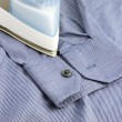 Stock Photo: Steam iron on blue shirt