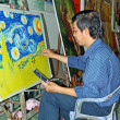 Постер, плакат: Artist Paints Van Gogh Reproduction in HCMC Art Market