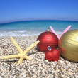 Christmas ornaments on the beach — Stock Photo #11623147