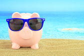 Summer piggy bank with sunglasses on the beach — Stock fotografie