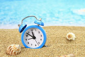Vacation time. Alarm clock on the sand — Stok fotoğraf
