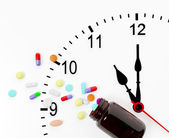 Clock and pills come out from a medicine bottle — Stock Photo
