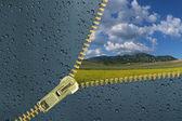 Unzipped glass with water drops revealing beautiful landscape — Stock Photo