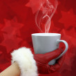 Woman&amp;#039;s hand with red glove holding a cup of coffee - Foto Stock
