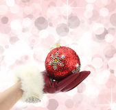 Woman's hand with red glove holding a Christmas ball — Stok fotoğraf